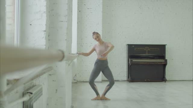 balettdansare utför demi plattång motion på barre - balettstång bildbanksvideor och videomaterial från bakom kulisserna
