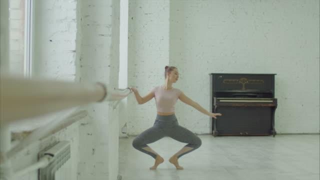 balettdansare utför grand plattång motion på barre - balettstång bildbanksvideor och videomaterial från bakom kulisserna