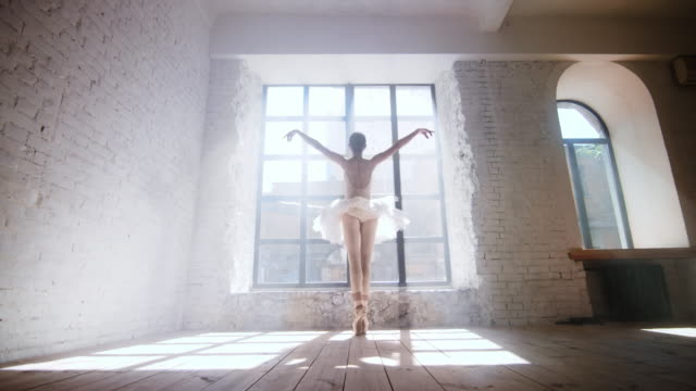 ballet dancer practicing in large studio near the window under day sun light - balet filmów i materiałów b-roll