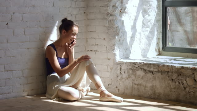 Ballet dancer sitting near the wall and speaking phone video