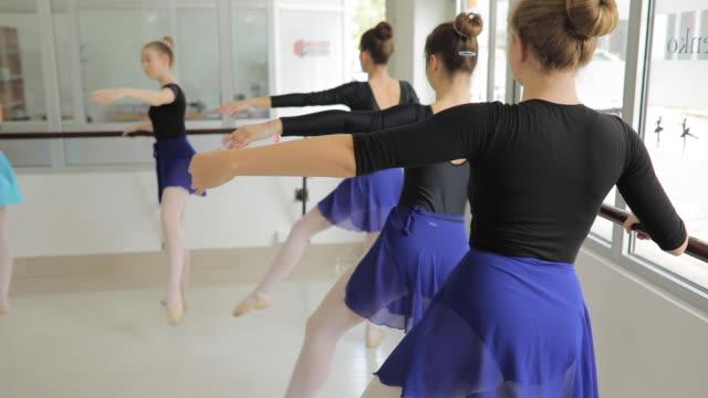 Ballet Dancers Exercising in Dance Studio Group of Ballet Dancers  Exercising in ballet  Studio,  using a barre ballet dancer stock videos & royalty-free footage