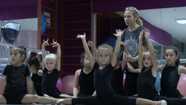 Ballet instructor teaches Ballet in school class Ballet instructor teaches Ballet in school class doing the splits stock videos & royalty-free footage