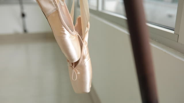 Ballet shoes hanging on a barre Ballet shoes hanging on a barre in a ballet studio, close up hanging stock videos & royalty-free footage