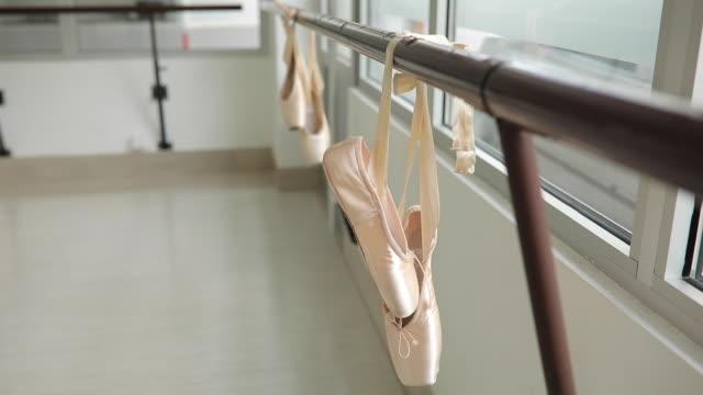 ballettschuhe hängen auf einer barre - ballettschuh stock-videos und b-roll-filmmaterial