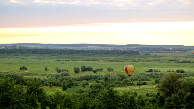 Balloon is preparing to take off at sunset. Air casovom on a green field video