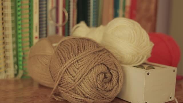 Balls of Yarn near Books. Close-Up.