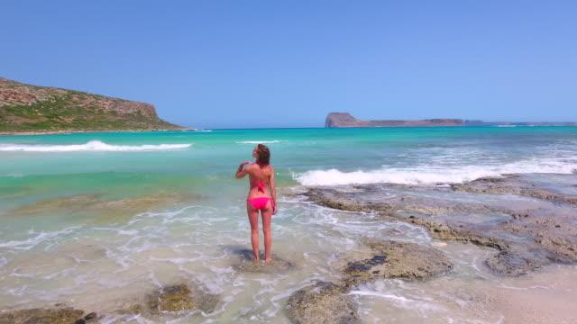 Balos Beach. Crete, Greece. The girl is walking along the seashore. Aerial drone shot. video
