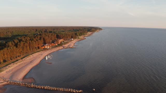 vídeos de stock e filmes b-roll de baltic sea shoreline sunset. smooth aerial drone motion. campsite coast. - letónia