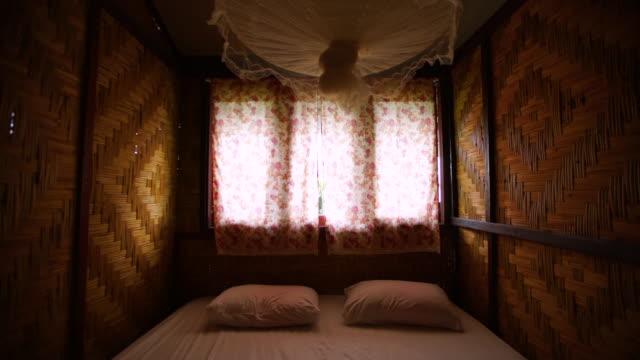 bambus bett zimmer tilt shot - moskitonetz stock-videos und b-roll-filmmaterial