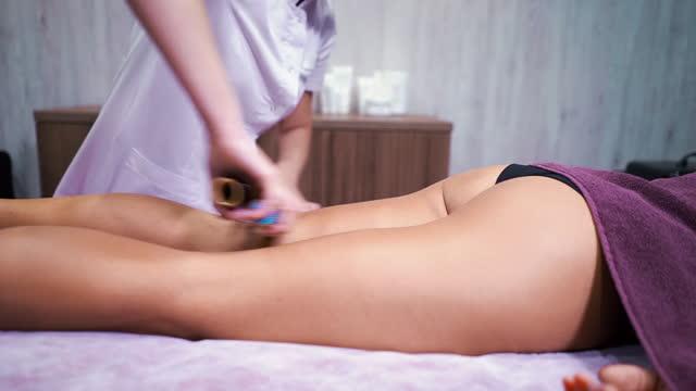 Bamboo sticks massage by therapist in wellness spa
