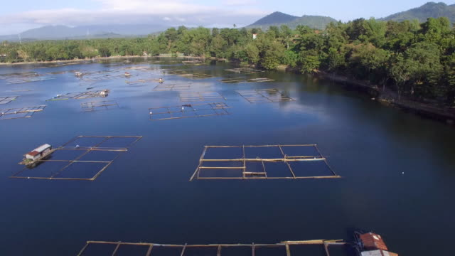 Bamboo structures built at the middle of the mountain lake. Drone aerial video