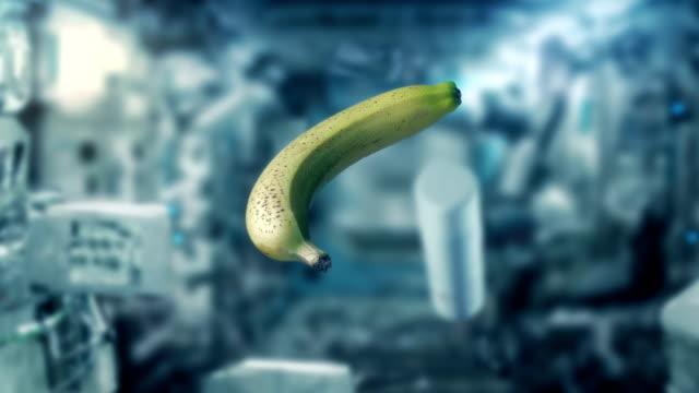 banana che galleggia a gravità zero nello spazio - campo gravitazionale video stock e b–roll