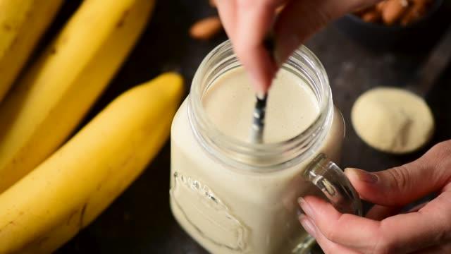 stockvideo's en b-roll-footage met banaan smoothie in glazen beker - milkshake