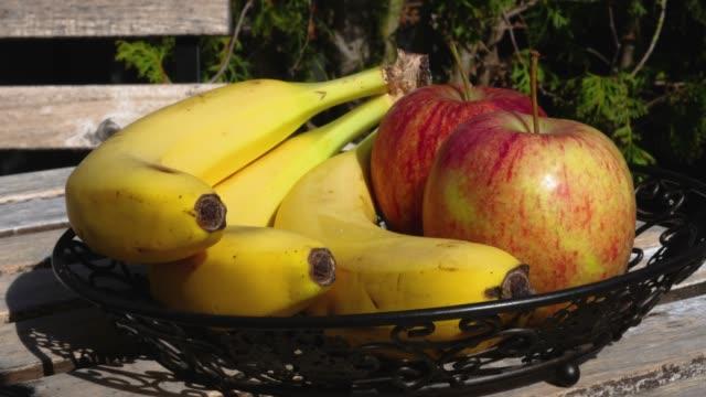 vídeos de stock e filmes b-roll de bananas and apples on outdoor table with shadows in time lapse - saladeira