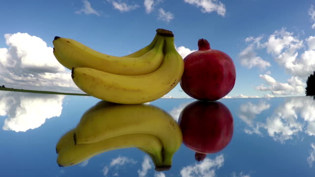 bananas and pomegranate placed on mirror glass under cloudy sky, time lapse video