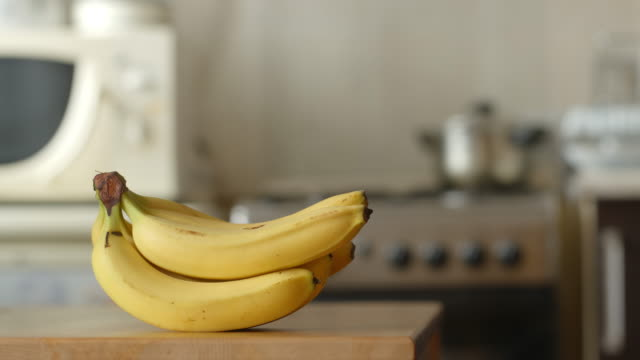 Bananas disappear on a table in a kitchen (stop motion) video
