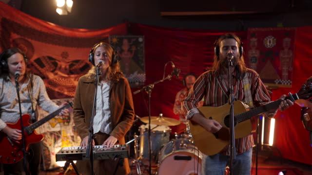 band njuter av att göra musik tillsammans på scenen - akustisk gitarr bildbanksvideor och videomaterial från bakom kulisserna