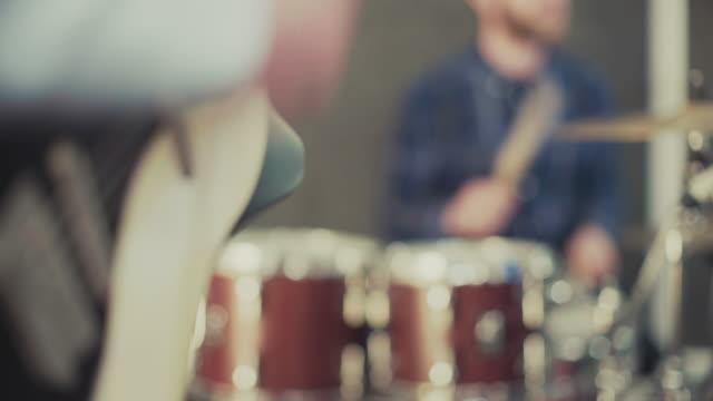 vídeos de stock e filmes b-roll de banda a tocar no estúdio de ensaio: guitarra e bateria - compositor