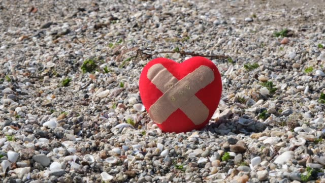 Band-aid covering a heart on the beach