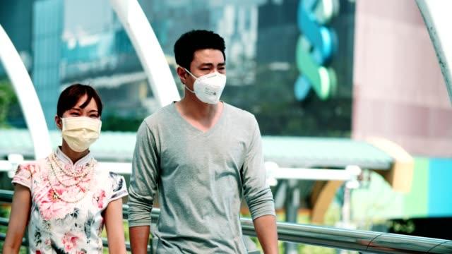 bangkok hava pullotion: genç çift ıstırap çekmek--dan yüz maskesi koruma ile öksürük - maske stok videoları ve detay görüntü çekimi