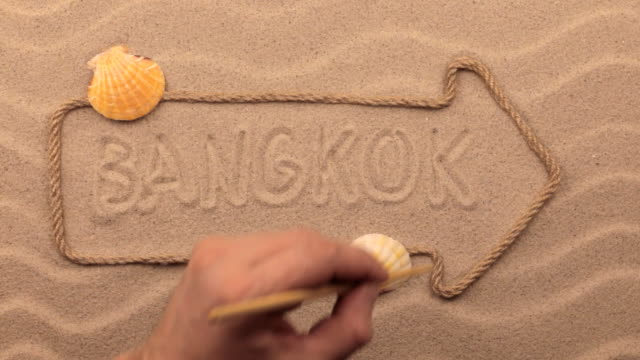 Bangkok inscription written by hand on the sand, in the pointer made from rope. video