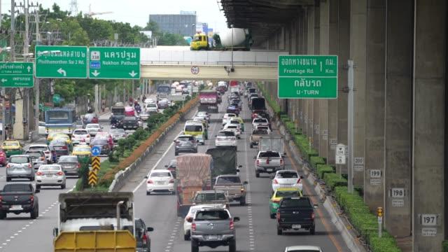 """""""bangkok, thailand - 19. august 2018: thailand straße namen thanon borommaratchachonnani mit den vielen autos am hinterteil und verkehr-schild und überqueren sie die straße in die straße am nachmittag."""" - editorial videos stock-videos und b-roll-filmmaterial"""