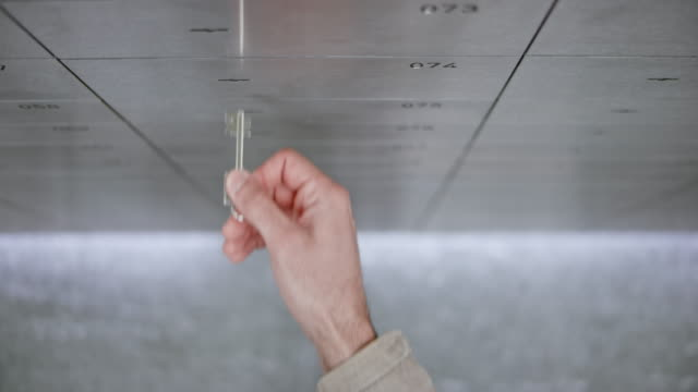DS Bank clerk opening a safe deposit box to grant access to a male customer using his own key to unlock it video