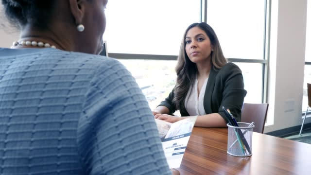 Bank customer discusses banking services with female employee