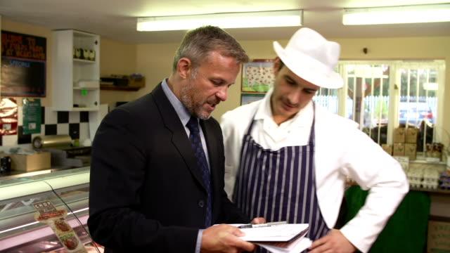 vidéos et rushes de directeur de banque réunion avec le propriétaire de magasin de bouchers - inspecteur