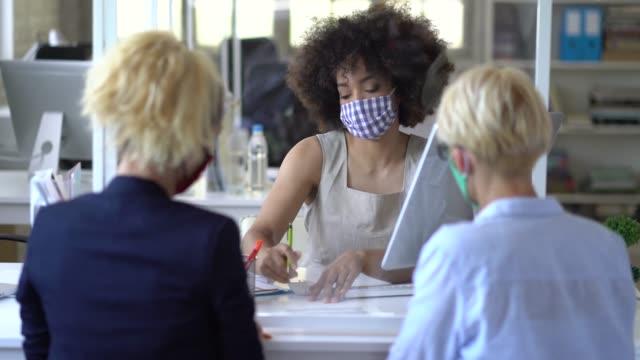 새로운 계약 체결을 위해 두 명의 여성 고객에게 조언하는 보호 얼굴 마스크를 착용한 은행 점사 - bank 스톡 비디오 및 b-롤 화면