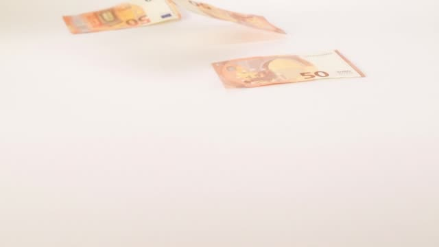 Banknotes of 50 values fly and drop on a white background