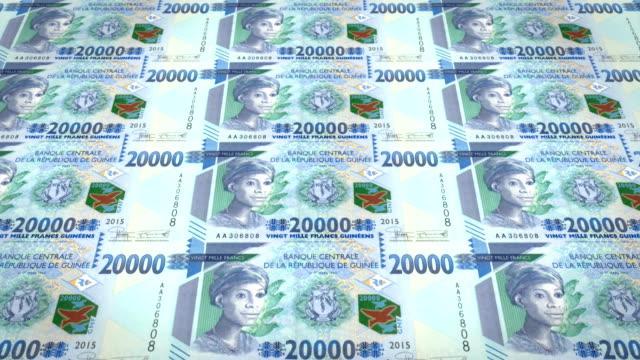Banknotes of twenty thousand guinean francs rolling, cash money, loop video