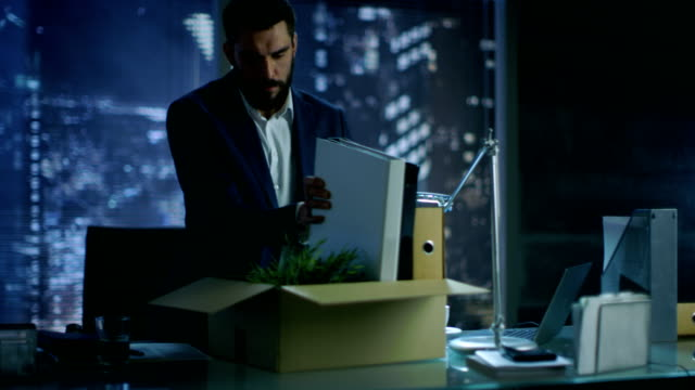 Konkurs Geschäftsmann sammelt seine Sachen in einen Karton Box und anschickt, seine Firma zu verlassen. Im Hintergrund Großstadt Fensteransicht. – Video
