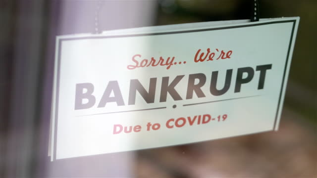 Bankrupt sign hang on the glass in pandemic time in 4K Slow motion 60fps
