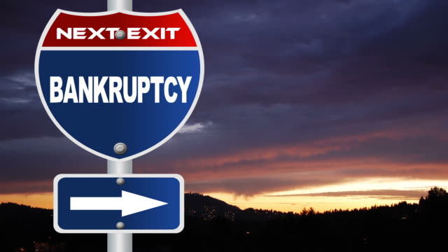 Bankruptcy road sign with flowing clouds video