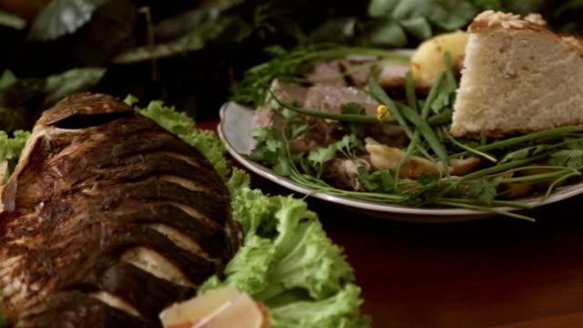 vidéos et rushes de table de banquet avec gros morceau de viande grillée avec laitue et tomates - banquet