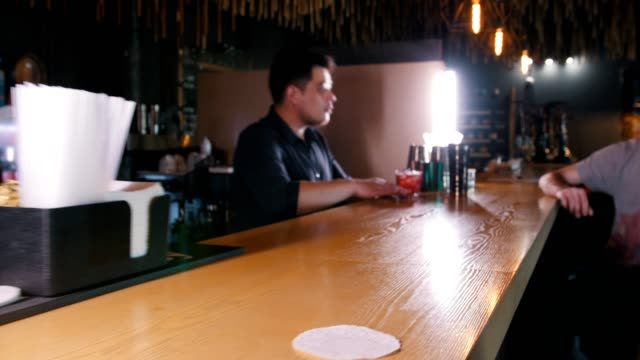 Bar concept - a person takes a glass from the counter, a young barman serves a cocktail to the visitor