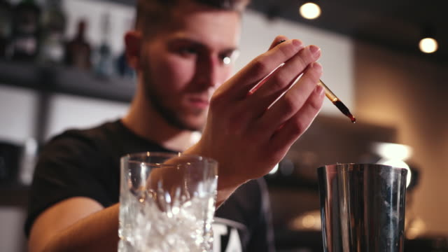 bar counter, bartender using shaker and various ingredients makes cocktail