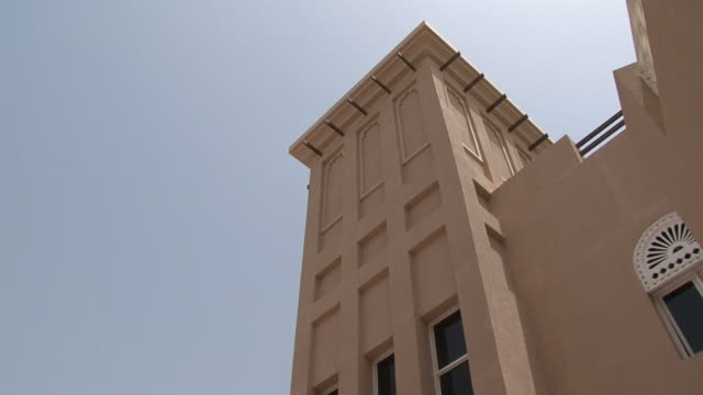 Barajeel Barajeel. Low-angle pan-left on a windtower or barajeel on the side of modern building. A traditional Persian influenced architectural design creating natural ventilation in buildings. dubai architecture stock videos & royalty-free footage