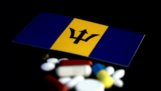 Barbados flag with lot of medical pills isolated on black background video