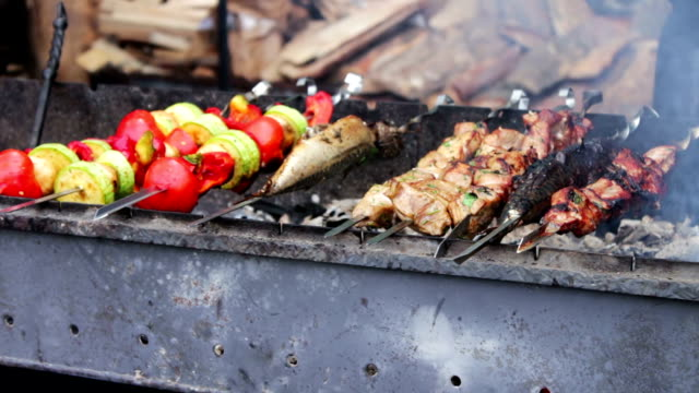 Barbecue fish, meat and vegetables roast on the grill.Street Food, Fast Food, Snack on the street, taseful, delicious video
