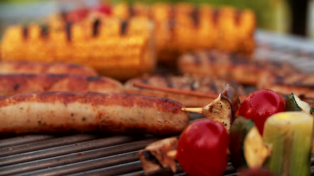 Barbecue grill with sausages, chicken and vegetables being cooked video