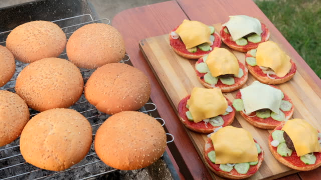 Barbecue grilled meat for hamburgers. Man making delicious sandwich. Preparation of tasty but unhealthy fast food, outdoors in summer day Hamburger holiday menu. Burgers are prepared in outdoors from buns, fried cutlets, vegetables, slice of cheese, tomato, ketchup, sauce. Chef man preparing the fresh burger. 4K UHD video bun bread stock videos & royalty-free footage