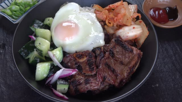 Barbecue Korean short ribs - Bibimbap Bowl Assembling a Korean Bibimbap Bowl. BBQ Korean Short Ribs with Kimchee and a fried Egg. ready to eat stock videos & royalty-free footage