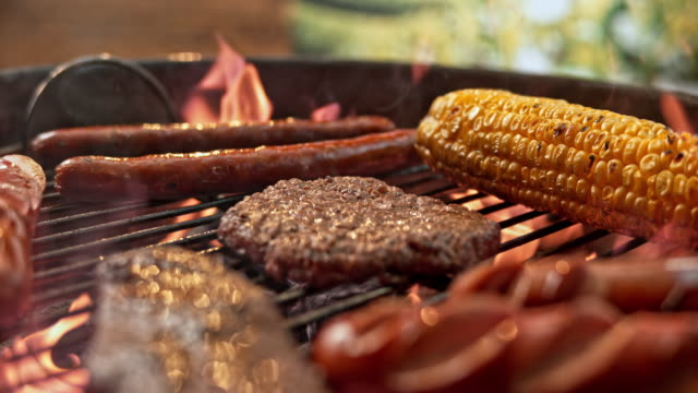 slo mo tu barbecuing meat and corn - alla griglia video stock e b–roll