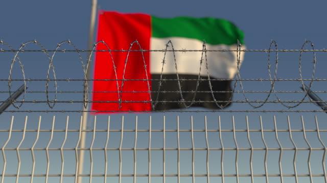 barbed wire against waving flag of the uae - uae flag filmów i materiałów b-roll