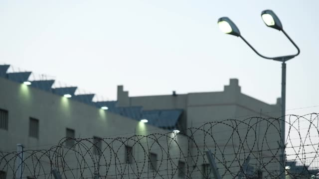 Barbed wire and light pole