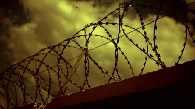 taggtråd överst på staketet mot den dystra, mörka himlen med moln. skott i rörelse - järn bildbanksvideor och videomaterial från bakom kulisserna