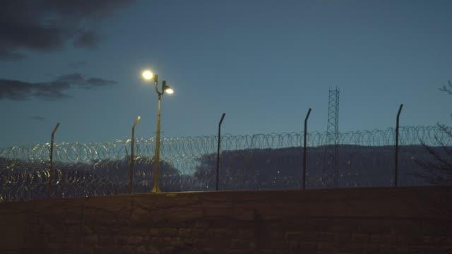 """vídeos y material grabado en eventos de stock de esgrima de alambre de púas al anochecer alrededor de la penitenciaría de los estados unidos, centro administrativo máximo de la prisión de supermax en florencia, colorado (condado de fremont)-el """"alcatraz de las rocosas"""" - valla límite"""