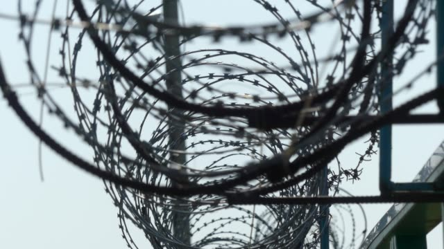 vídeos y material grabado en eventos de stock de alambre de púas de la cerca. cerca de la prisión. - valla límite